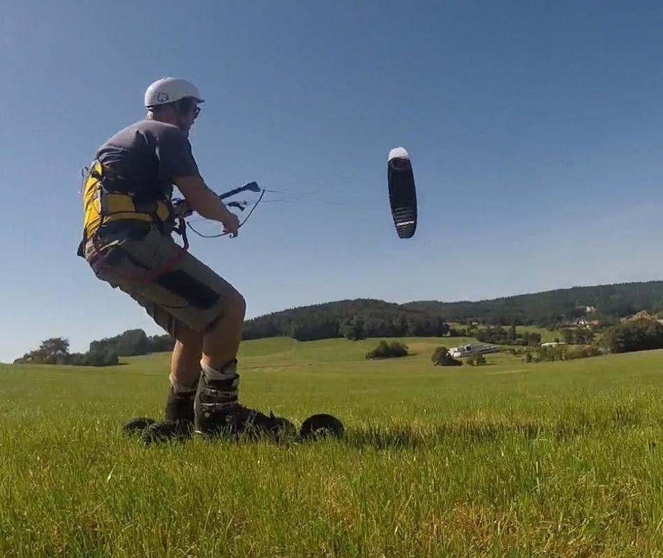 Mit den FLXRIDE Land Kite Skates auf der Wiese und dem schwarzen Drachen Hyperlink V2 von Ozonekites am blauen Himmel.