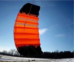 Der Trainerkite Ignition V2 von Ozone Kites benutzen wir in der Kiteschule um den Kindern und vorsichtigen Kitern das Kiten beizubringen. Hier sieht man den Kite beim Einsatz im Winter beim Snowkiten.