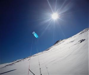 Das Bild zeigt einen blauen Kite ExploreV1 auf einem Berg mit weißem Schnee. Im Hintergrund ist der Himmel blau.