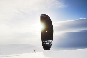 Auf dem Bild sieht man den neuen HyperlinkV2 von Ozone Kites beim Snowkiten. Der Kite ist in schwarz. Er eignet sich auch zum Kitesurfen, Landkiten und snowkiten.
