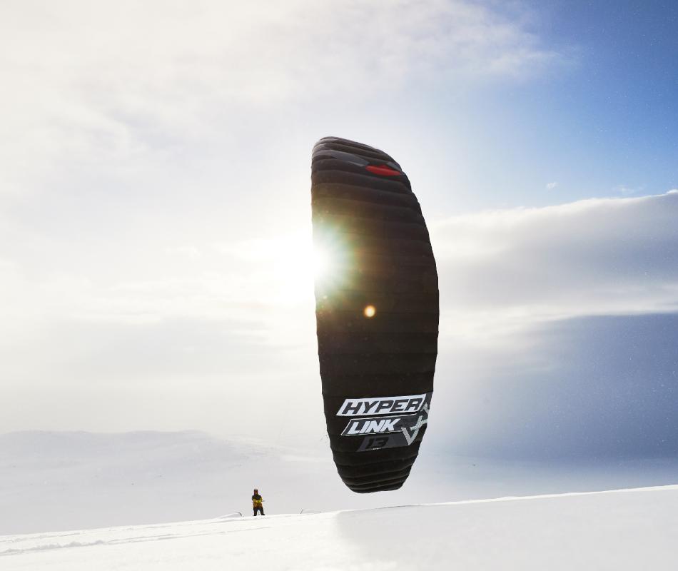 Auf dem Bild sieht man den neuen HyperlinkV2 von Ozone Kites beim Snowkiten. Der Kite ist in schwarz. man kann mit ihm gut Grasskikiten, Kitesurfen, Landkiten und snowkiten.