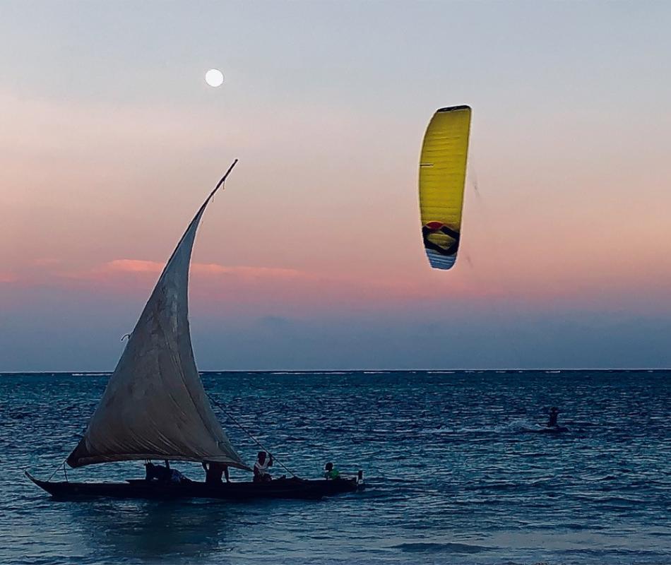 Ein gelber Kite ChronoV3 von Ozonekites am Abendhimmel vor dem Wasser. Im Vordergrund ist ein Segelboot zu sehen. Der Kite ist gut geeignet zum Kitesurfing auf dem Wasser.