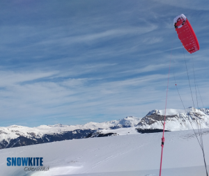 Das Bild zeigt einen roten Kite ExploreV1 von Ozonekite auf einem Berg mit weißem Schnee am Boden. Im Hintergrund sieht man einen bewölkten Himmel.