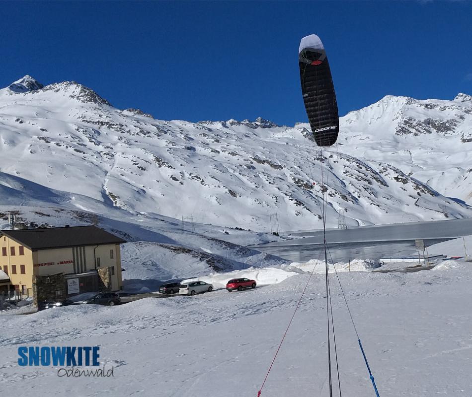 Das Bild zeigt einen schwarzen Kite HyperlinkV2 von Ozonekite vor dem weißen Berg mit einem Haus im Vordergrund. Im Hintergrund sieht man den blauen Himmel und einen blauen See.