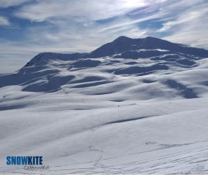 Das Bild zeigt einen roten Kite SubzeroV1 von Ozonekites auf weißem Schnee in den Bergen.