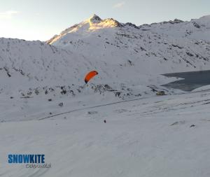 Das Bild zeigt einen roten Kite SubzeroV1 von Ozonekite vor weißem Schnee in den Bergen.