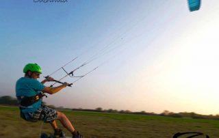 Das Bild zeigt einen blauen Kite ExploreV1 am blauen Himmel. Der Kite zieht einen Menschen auf einem Trampa Kitelandboard über eine grüne Wiese.
