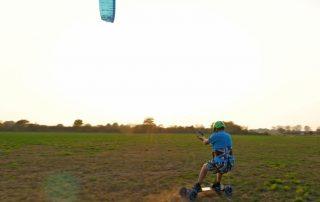 Das Bild zeigt einen blauen Kite ExploreV1 vor dem weisen Himmel. Der Kite zieht den Kite auf dem Mountainboard über die grüne Wiese.. Der Berg heiß Ätna und ist ein Berg in Sizilien.