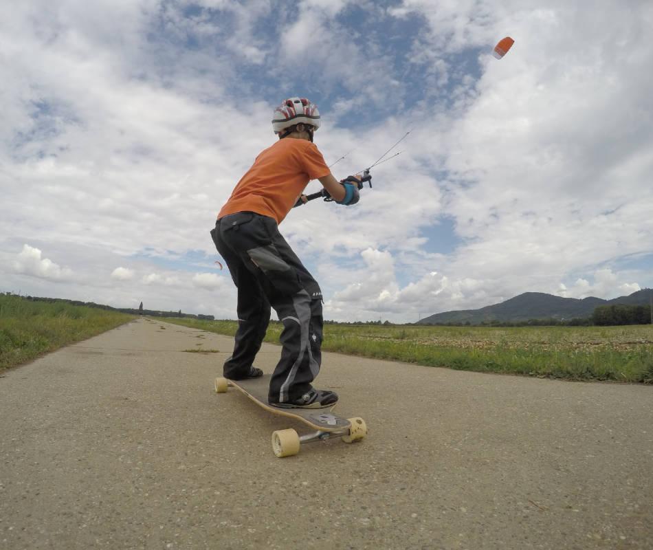 Auf dem Bild sieht man den orangefarbenen IgnitionV2 von Ozonekites vor den Wolken. Der Kite zieht einen Jungen auf dem Skateboard.