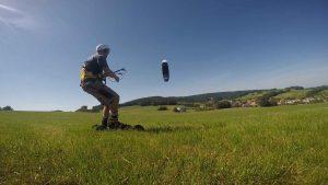 Der Kiter fährt auf Flxride Landkte Skates über die grüne Wiese und wird von einem schwarzen Kite am Himmel gezogen.