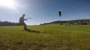 der Kiter wird durch den Kite HyperlinkV2 von Ozonekites auf den Flxrides über eine grüne Wiese gezogengezogen.